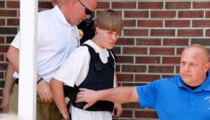 Police lead suspected shooter Dylann Roof, 21, into the courthouse in Shelby, North Carolina, June 18, 2015.   Roof, a 21-year-old with a criminal record, is accused of killing nine people at a Bible-study meeting in a historic African-American church in Charleston, South Carolina, in an attack U.S. officials are investigating as a hate crime.  REUTERS/Jason Miczek