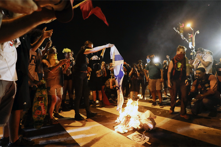 Demonstrators burn a flag during a protest in Philadelphia, Tuesday, July 26, 2016, during the second day of the Democratic National Convention. (AP Photo/Matt Slocum)
