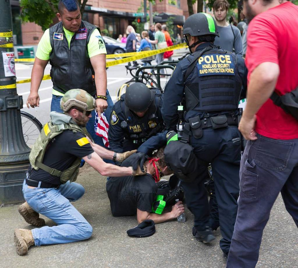 A III% militia member aids police and DHS agents in the arrest of an anti-fascist protester at Joey Gibson's rally on 6/4/2017 in Portland. This instance of police / federal agent / militia collaboration is currently under investigation by the U.S. Attorney's office. We aren't holding our breath